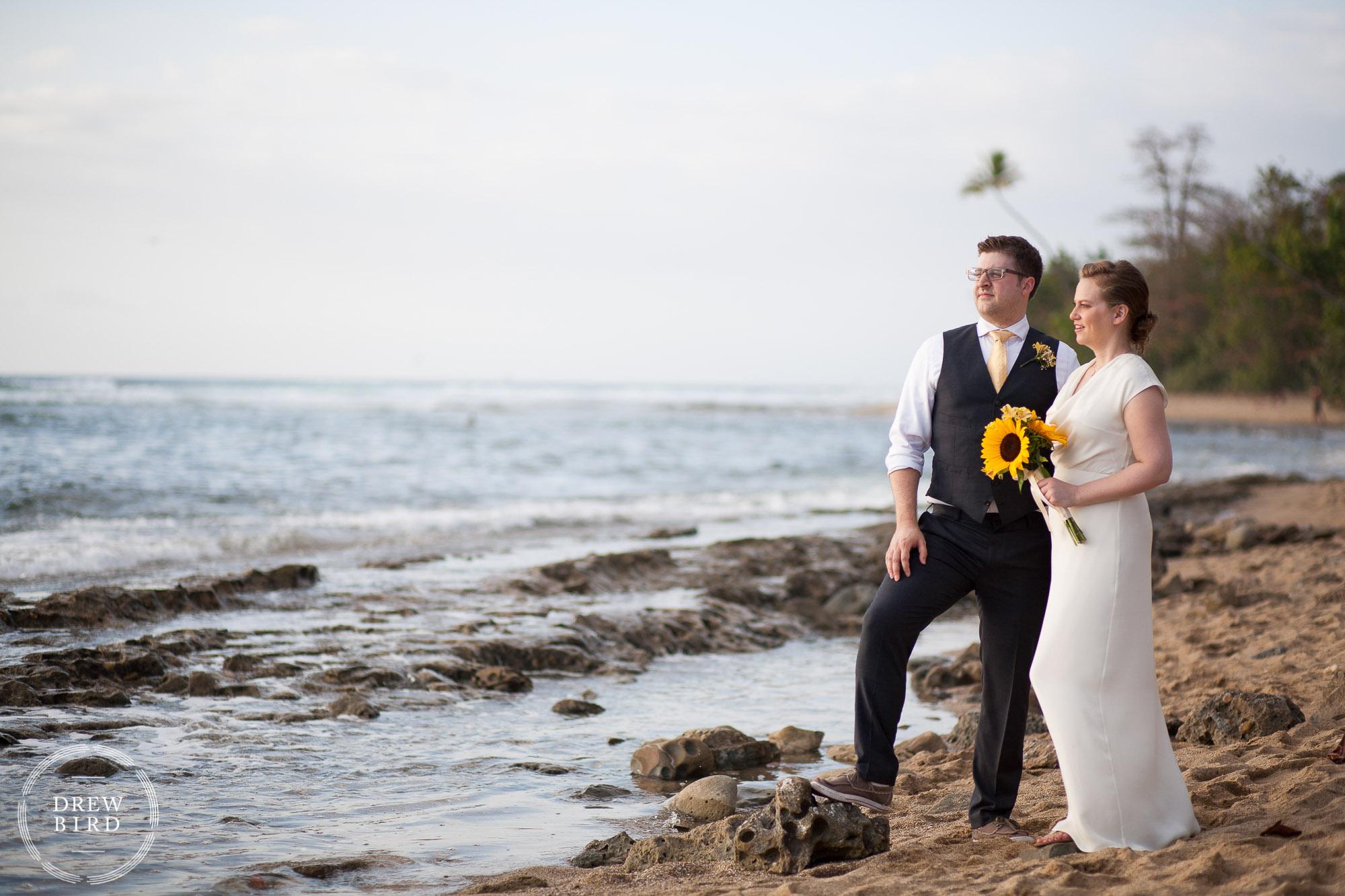 Bride and groom standing on the beach at ocean's edge. Creative portrait. Rincon Puerto Rico beach wedding. Destination wedding photographer Drew Bird. Villa Playa Maria wedding photography.