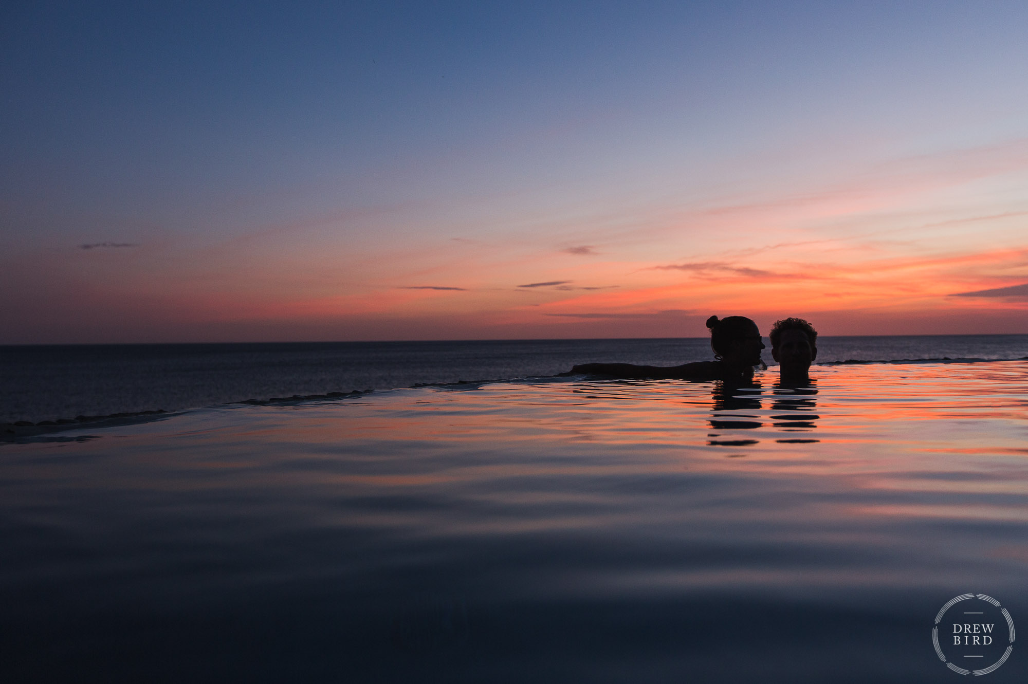 Bride and groom in an infinity pool at sunset with silhouette. Rancho Santana Nicaragua destination wedding photographer Drew Bird.