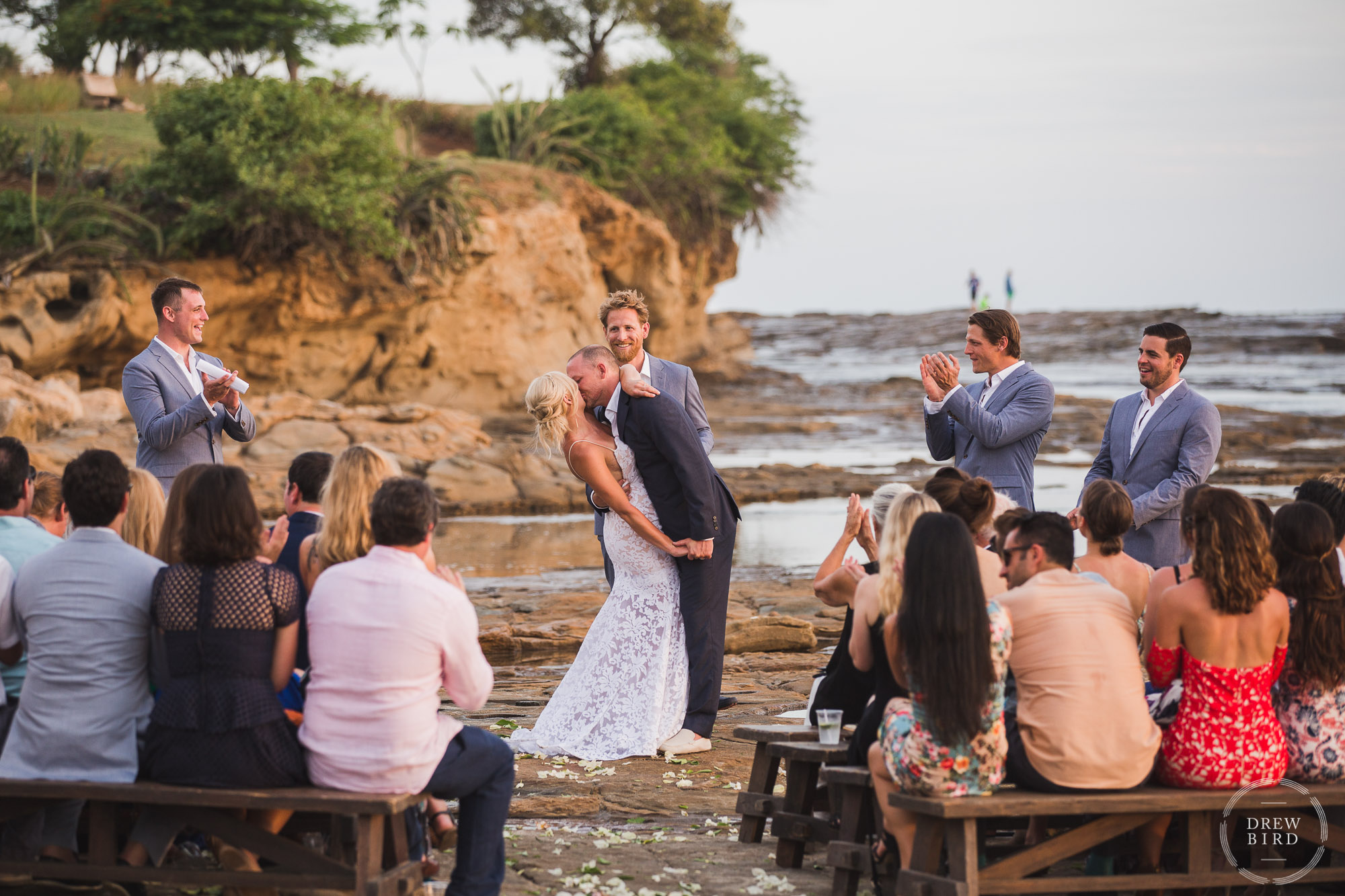 Intimate wedding ceremony on tidal rocks on the beach at sunset. Rancho Santana Nicaragua destination wedding photographer Drew Bird.
