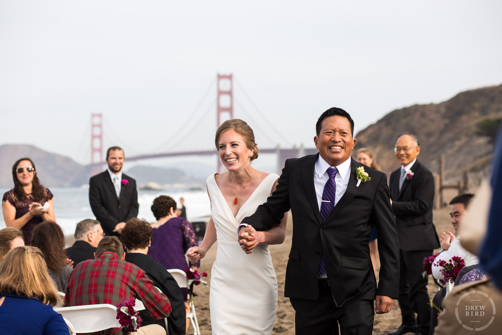 Bride and groom holding hands laughing walking down aisle. Baker Beach wedding ceremony. San Francisco wedding photojournalist Drew Bird Photo.
