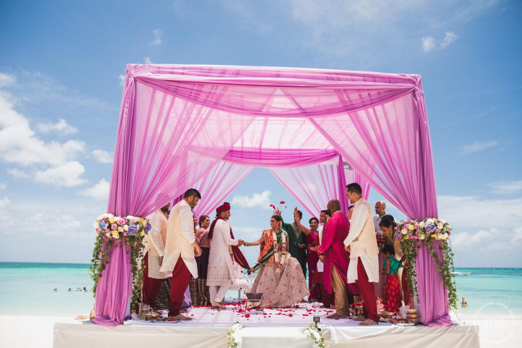 Indian bride and groom on mandap during Saptapadi. Indian Hindu beach wedding. Hilton Aruba destination wedding photographer. San Francisco wedding photojournalist Drew Bird.