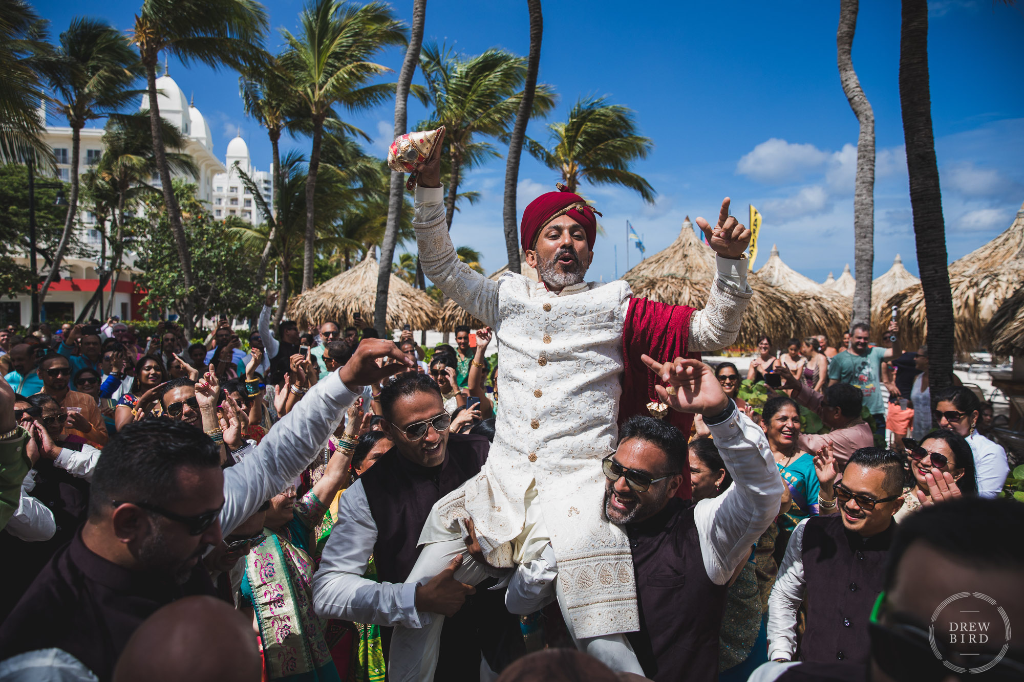 Groom carried by his friends during the Baraat. Indian Hindu wedding. Hilton Aruba destination wedding photographer. San Francisco wedding photojournalist Drew Bird.