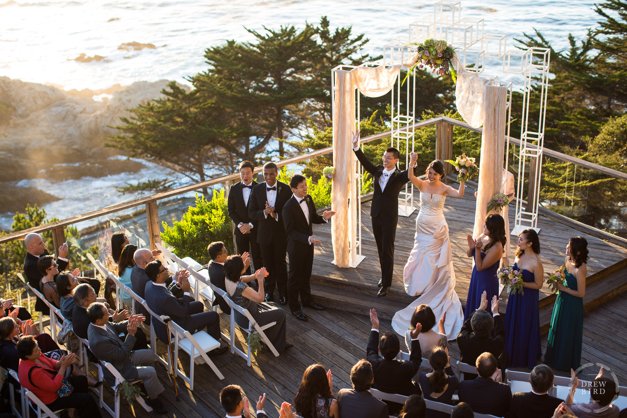 Bride and groom with arms raised up in the air during wedding ceremony. Hyatt Carmel Highlands outdoor wedding with pacific ocean. Big Sur, California wedding. San Francisco wedding photojournalist Drew Bird Photo.