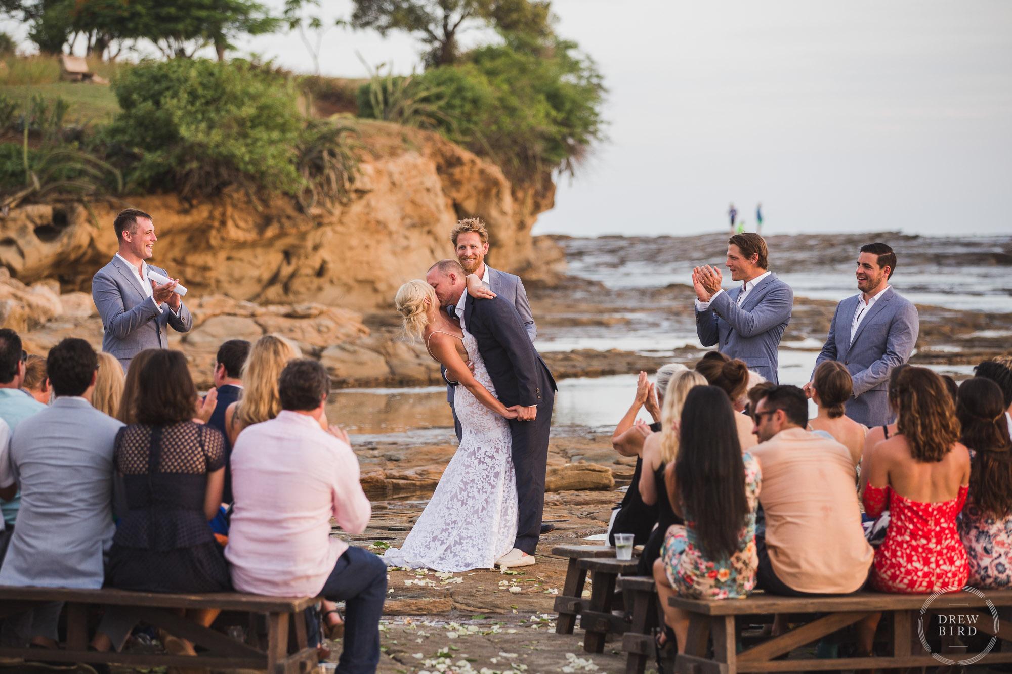 Bride and groom kissing during sunset beach wedding ceremony on tidal rocks Rancho Santana Nicaragua destination wedding photographer. San Francisco wedding photojournalism by Drew Bird Photo.