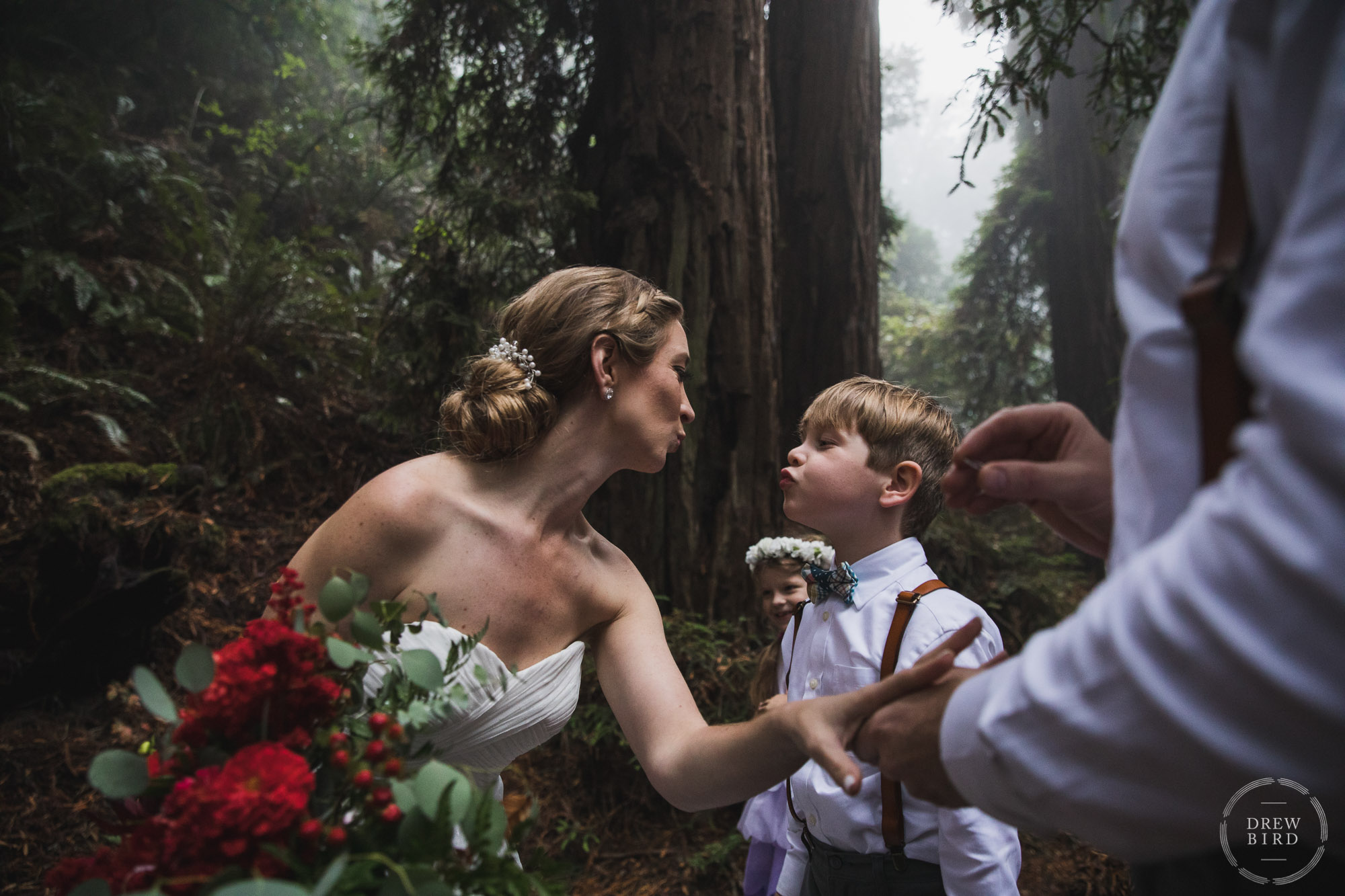 Bride leans over to kiss ring bearer during redwood forest elopement wedding ceremony. San Francisco wedding photojournalism by Drew Bird Photo.