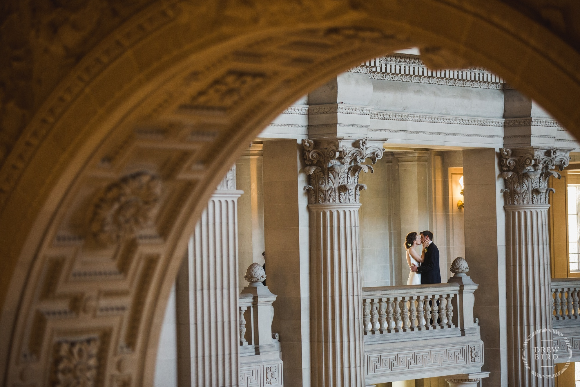 Bride and groom wedding portrait with arches architecture. San Francisco City Hall wedding photographer Drew Bird.