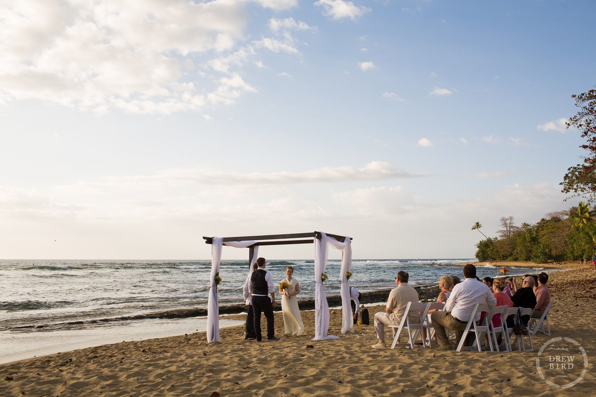 Beach wedding ceremony. Bride and groom standing in sand under chuppah. Villa at Maria's Beach. Rincon, Puerto Rico destination wedding photographer Drew Bird.
