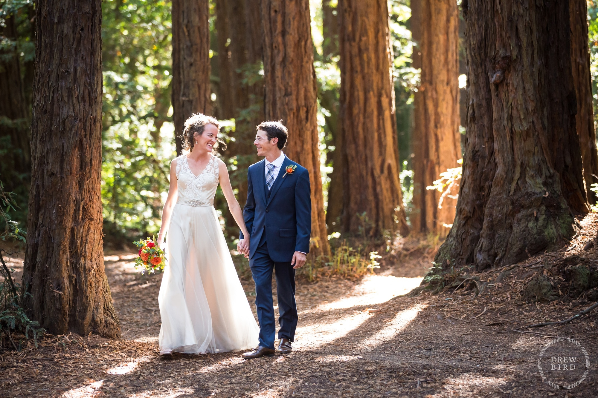 Bride and groom walking through a redwood forest with great light. Creative wedding portrait. Oakland California wedding photographer Drew Bird.