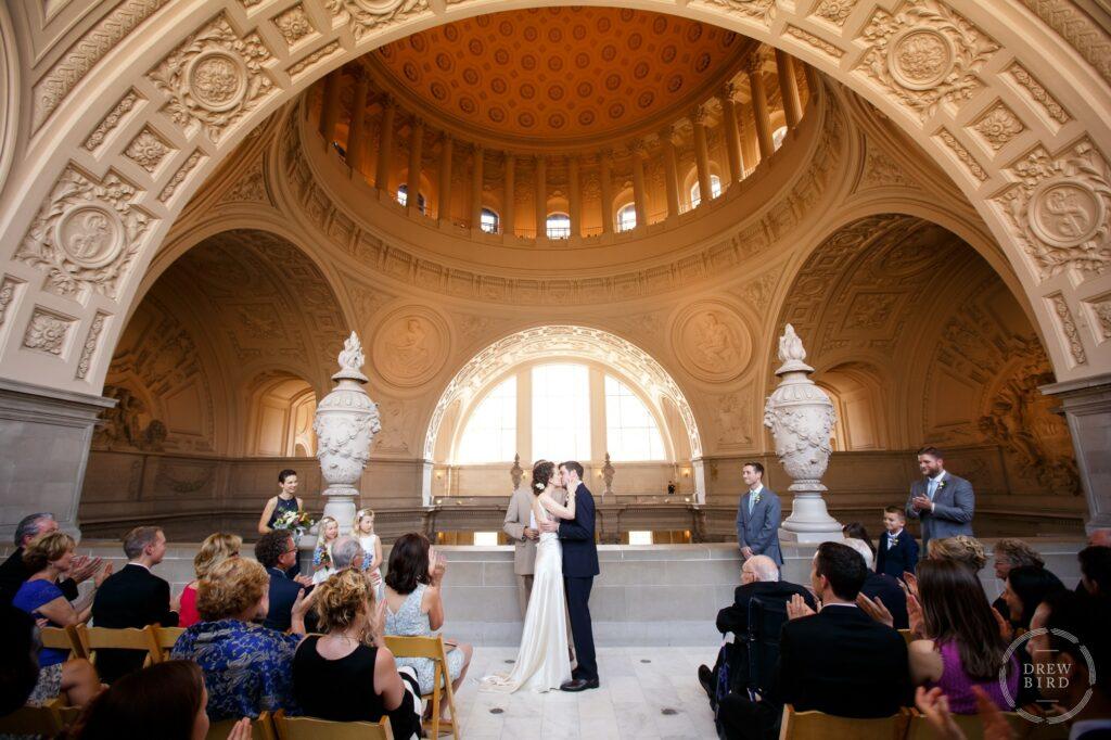 Bride and groom kiss amazing architecture. Ceremony 4th floor Mayor's balcony San Francisco City Hall wedding photographer Drew Bird.