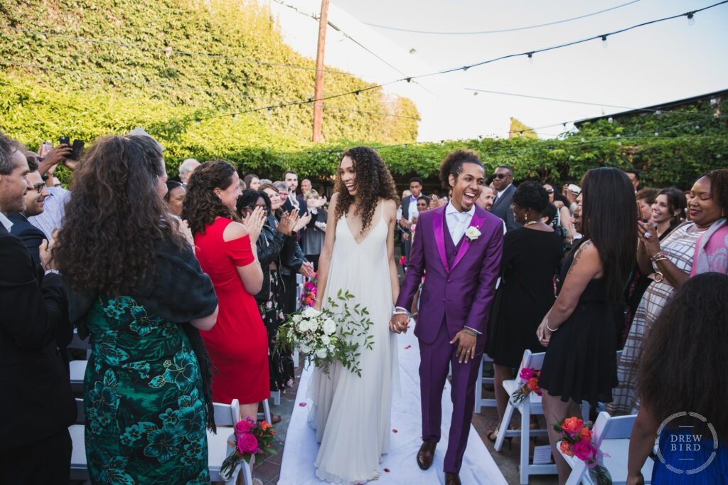 Bride and groom walking down the aisle laughing with guests cheering. Outdoor wedding ceremony at Seventh Place. Los Angeles wedding photojournalism by Drew Bird.