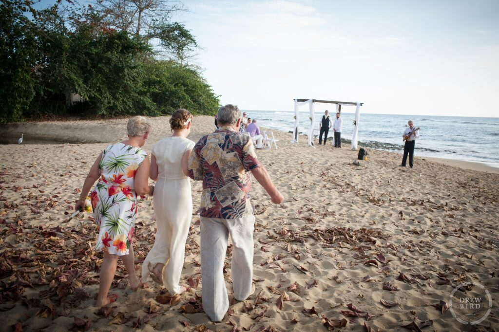 Bride walking to ceremony arm in arm with her parents. Destination wedding at the Villa at Maria's Beach in Rincon, Puerto Rico. Wedding photojournalism by Drew Bird.