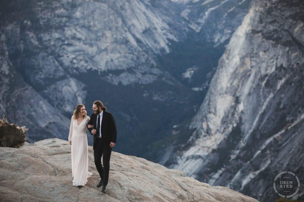 Bride and groom walk on cliff edge at glacier point. Yosemite National Park wedding elopement. Oakland micro wedding photographer Drew Bird.