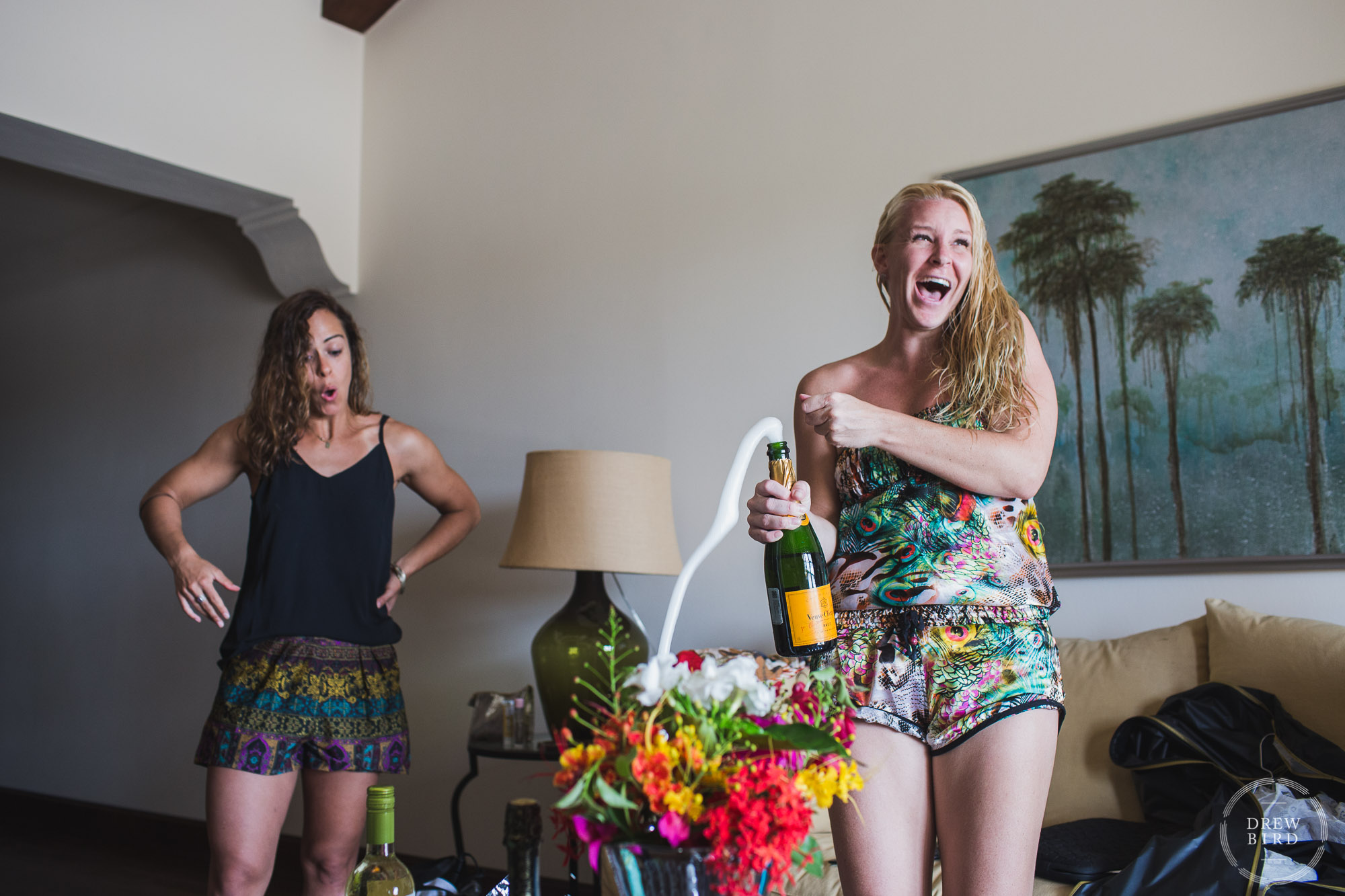Bridesmaid with overflowing champagne bottle. Rancho Santana Nicaragua destination wedding photographer Drew Bird.